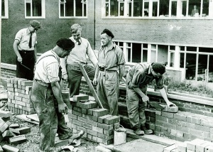 The MIRACLE WORKERS: full steam ahead for the 1951 Festival of Britain, the wonder team gets on with the job of the second instalment for the new County Architect's Dept at Wakefield. Picture shows Mr Hubert Bennett, WR County Architect wearing the white jumper (responsible for the revolutionary design) having an on-the-spot consultation, with (left to right) bricklayer George Kemp, labourer Clarry Barraclough, brick-layer foreman Geoffrey Garbett, and his son Geoffrey Arthur Garbett.